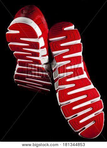 Sneaker sole view of a falling foot from below