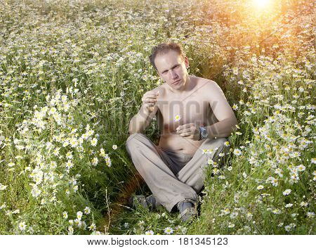 man in the field of camomiles guesses on a camomile