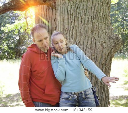 man and woman near an oak in summer day something was seen aside and looked scaredly and with astonishment