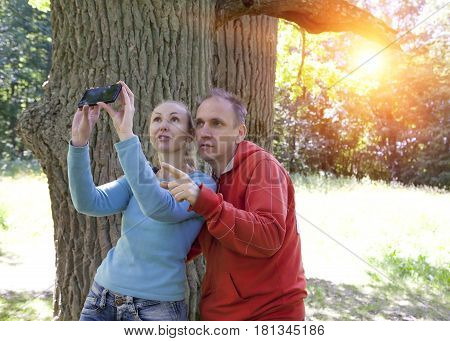 man and woman near an oak in summer day show up and photograph on phone