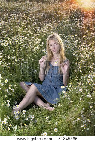 beautiful woman in the field of camomiles guesses on a camomile