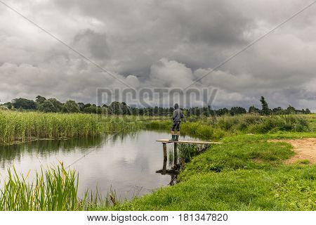 Teen boy fishing on wooden pier with dramatic gloomy sky
