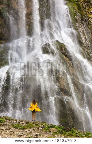 Beautiful view on mountain waterfall with woman's small figure on foreground
