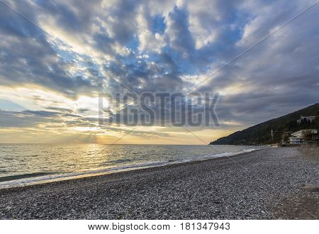 Beautiful sunset over the sea with pebble beach