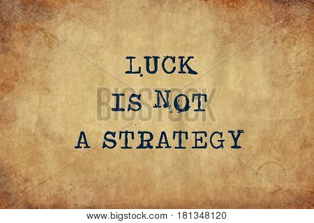 Inspiring motivation quote of luck is not a strategy with typewriter text. Distressed Old Paper with Typing image.