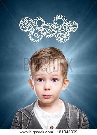 A conceptual image of an intelligent child who thinks about looking at gears