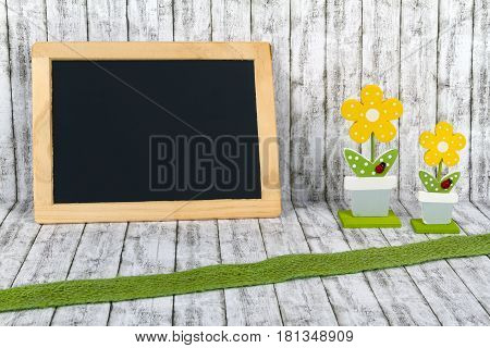 Blank Blackboard with decorative handmade Flowers on structure background