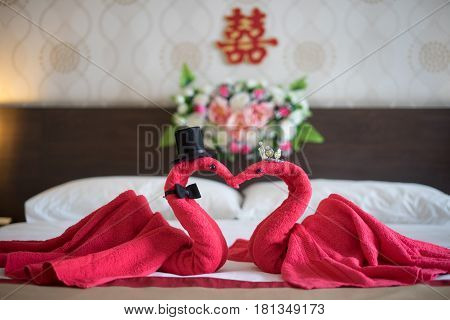 Two swans made of towels forming heart shape on bed in honeymoon suite room hotel decorated for wedding preparation decoration