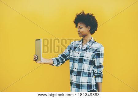 Beautiful smiling Brazilian teenager girl in checkered shirt having video call using digital tablet young attractive black female with curly afro hair making selfie on touch pad on yellow background