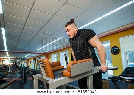 Focused man doing dips in the gym.