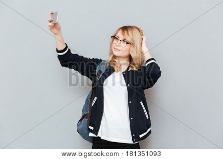 Student straighten hair while making selfie using smartphone isolated