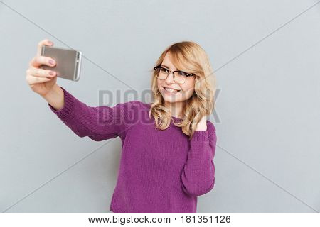 Blonde female student straighten her hair making photo using smartphone isolated
