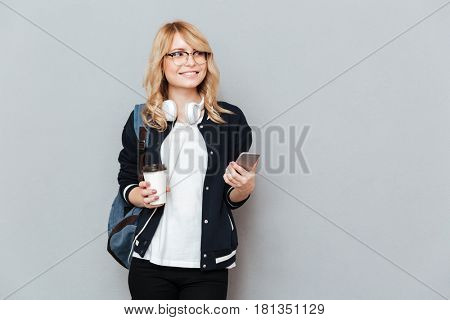 Happy female student in eyeglasses  and with backpack holding cup of coffee and  smartphon in hands while looking away