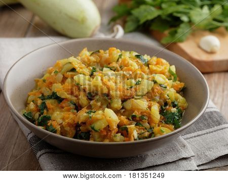 Summer squash and carrot ragout with parsley on a rustic table