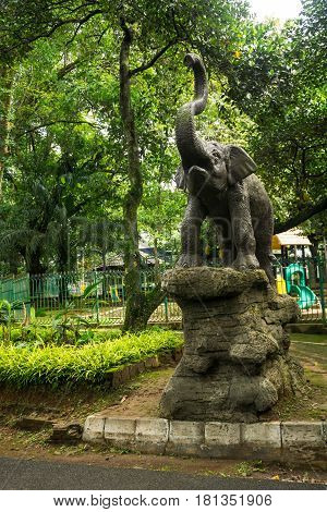 elephant statue standing on rock in front of children playground photo taken in Ragunan zoo Jakarta Indonesia java
