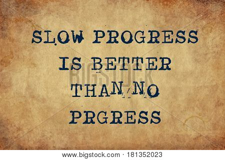 Inspiring motivation quote of slow progress is better than no progress with typewriter text. Distressed Old Paper with Typing image.