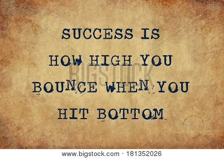 Inspiring motivation quote of success is how high you bounce when you hit bottom with typewriter text.  Distressed Old Paper with Typing image.