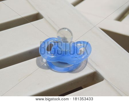 An isolated blue baby pacifier on the plastic surface