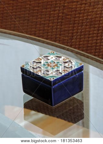 Small decorated box on a glass surface