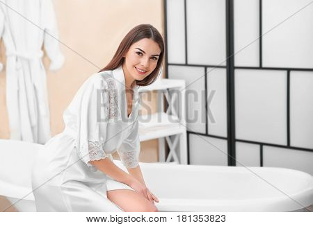 Beautiful young woman in dressing-gown going to take a bath at home