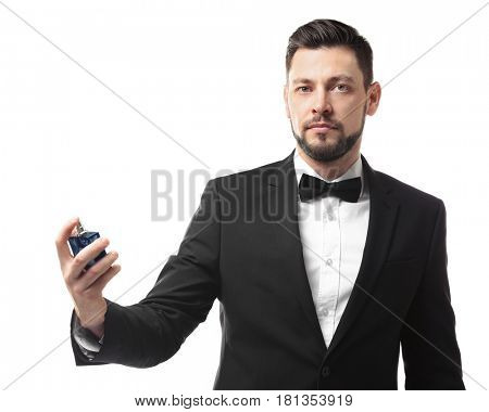 Handsome young man using perfume on white background