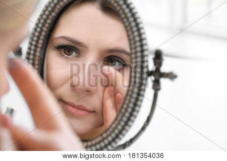 Woman putting contact lenses in front of mirror at home