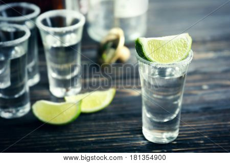 Tequila shot with lime slice and salt on table