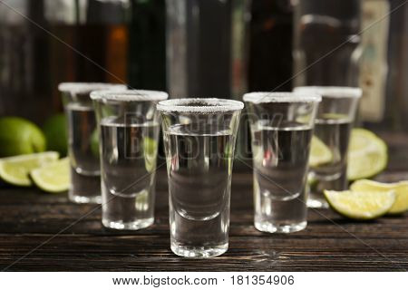 Tequila shots with lime slices and salt on table
