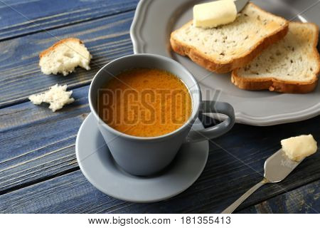 Composition with tasty butter coffee and toasts on wooden table
