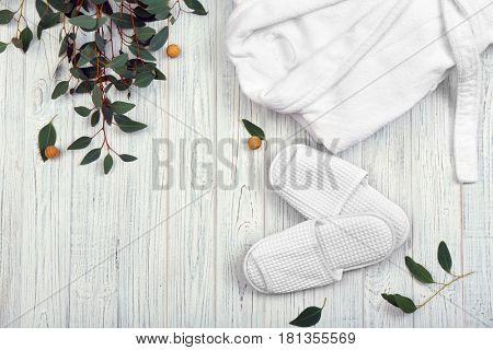 Beautiful composition with bathrobe and slippers on wooden background