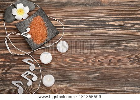 Beautiful spa composition with earphones and music notes on wooden background