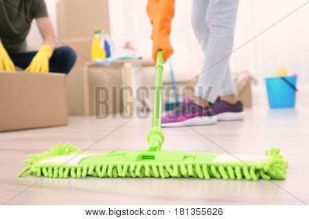 Woman moping floor in home, closeup