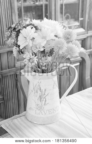 Spring flowers in watering can on country dining table light and airy black and white art composition