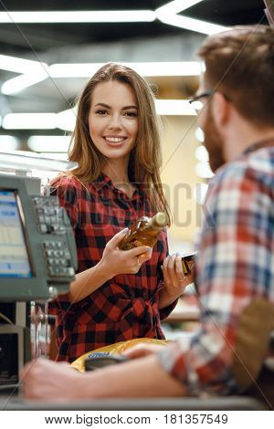 Image of smiling young lady standing in supermarket shop near cashier's desk. Looking at camera.