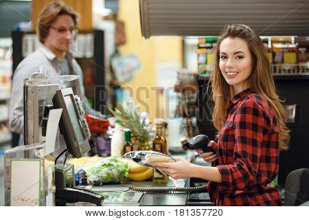 Picture of smiling cashier woman on workspace in supermarket shop. Looking at camera.