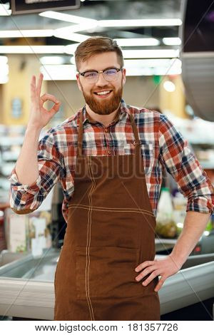 Image of cheerful cashier man on workspace in supermarket shop. Looking at camera showing okay gesture.