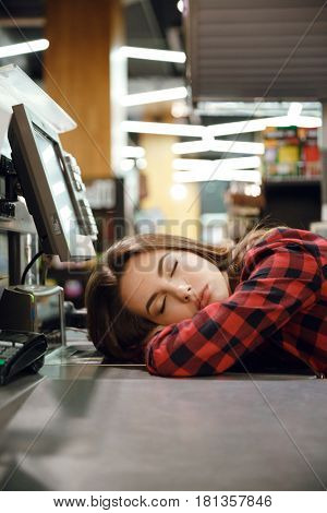 Image of cashier lady sleeping on workspace in supermarket shop. Eyes closed.