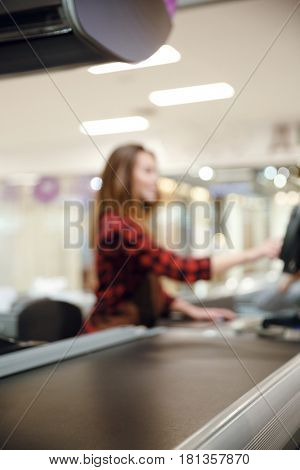 Blurred picture of cashier lady on workspace in supermarket shop. Focus on desk.