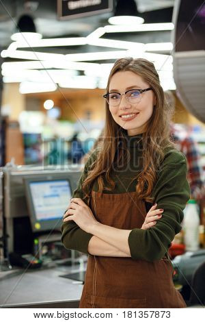 Image of happy cashier woman on workspace in supermarket shop. Looking at camera.