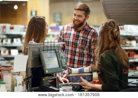 Picture of happy young loving couple standing near cashier's desk in supermarket shop. Looking aside.
