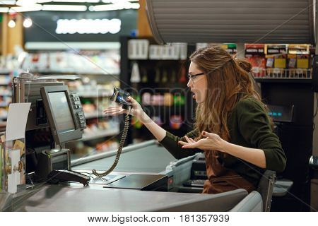 Side view picture of confused cashier woman on workspace in supermarket shop. Looking aside.