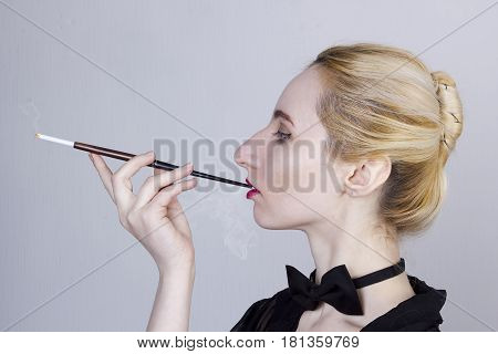 Young beautiful woman with a cigarette in the mouthpiece