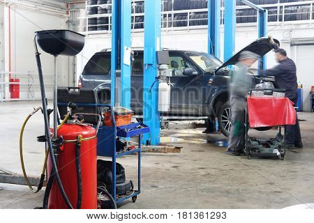 Stupino, Moscow region, Russia - April, 4, 2017: Interior of a car repair station in Stupino, Russia. There is a device for oil changing on the frontground