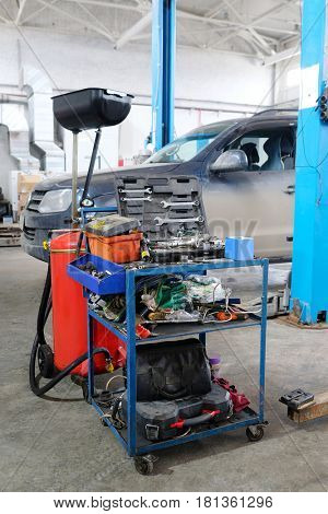 Stupino, Moscow region, Russia - April, 4, 2017: Interior of a car repair station in Stupino, Russia. There is a device for oil changing and tool's trolley on the frontground