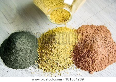Yellow red and black cosmetic cleansing clay for face and body. Healing Clay is a natural product. Dry cosmetic clay on a wooden background. Selective focus