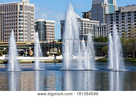 Multiple water fountains in from of towering building high rises