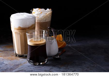 Coffee latte, black espresso and viennese coffee with whipped cream and orange zest