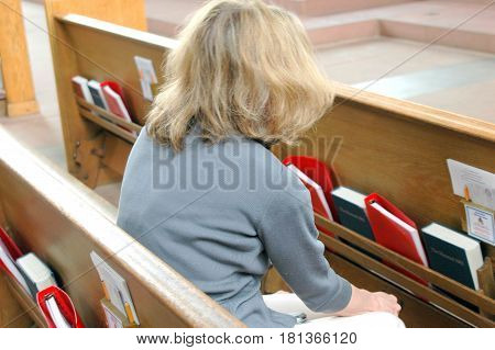 Mature female blond beauty attending church service during her lunch break.