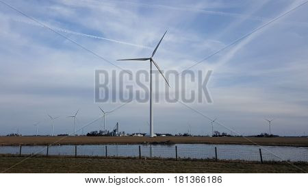 windmill farm wind turbine rotating above a farm under a blue and cloudy sky