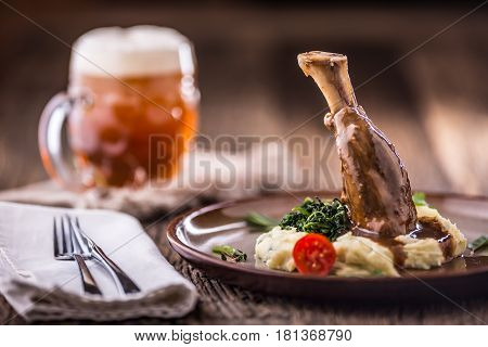 Lamb shank.Confit lamb shank with mashed potatoes spinach and draft beer in pup or restaurant.